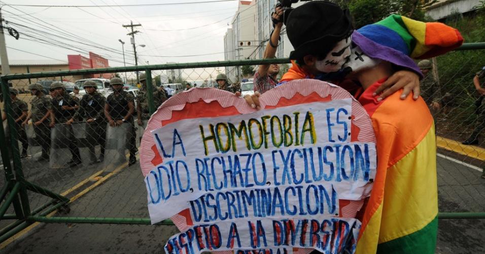 Casal gay se beija diante de soldados que fazem a segurança diante do palácio de governo, em Tegucigalpa, Honduras