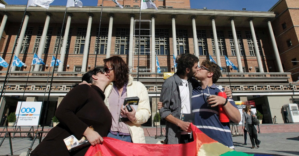 Dois casais beijam-se diante do prédio da prefeitura de Montevidéu, no Uruguai