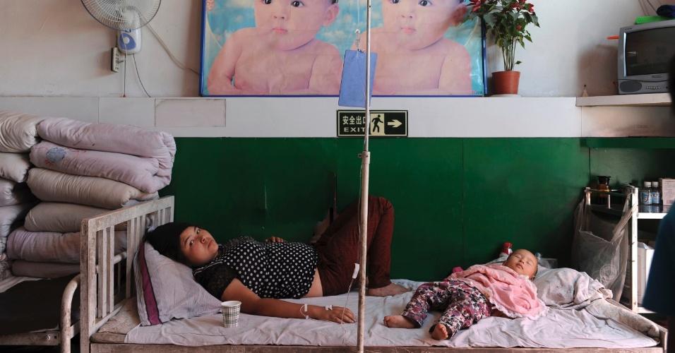 Mulher da etnia Uighur toma medicação na veia enquanto seu filho dorme em cama de hospital em Shaya, na Região Autônoma de Xinjiang