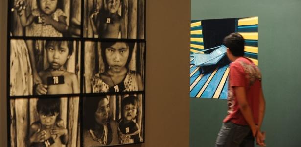 """Visitante passa por fotografias e quadros expostos na mostra """"Amazônia, ciclos de modernidade"""" - Antonio Scorza/AFP"""