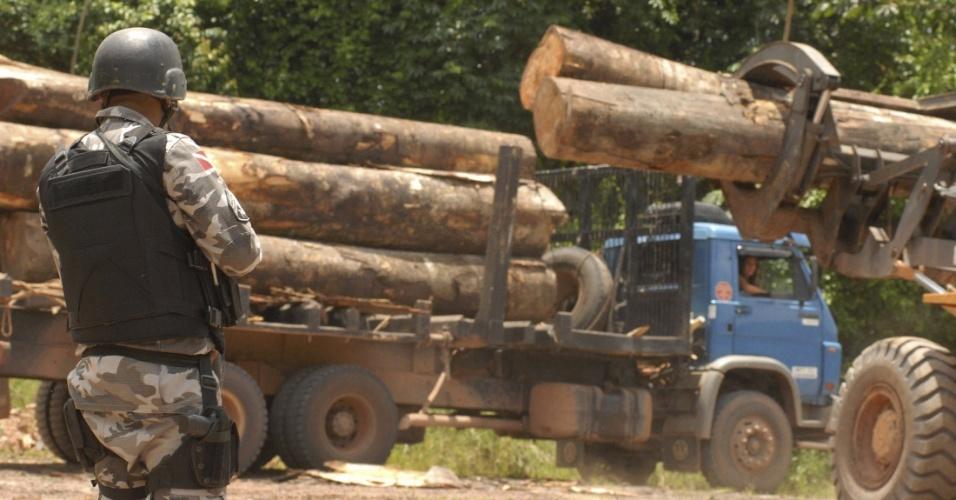 fev.2008 - Policial que integra forças federais enviadas a Tailândia, no Pará, para impedir conflitos com moradores, monta guarda em frente a caminhões que carregam madeira ilegalmente