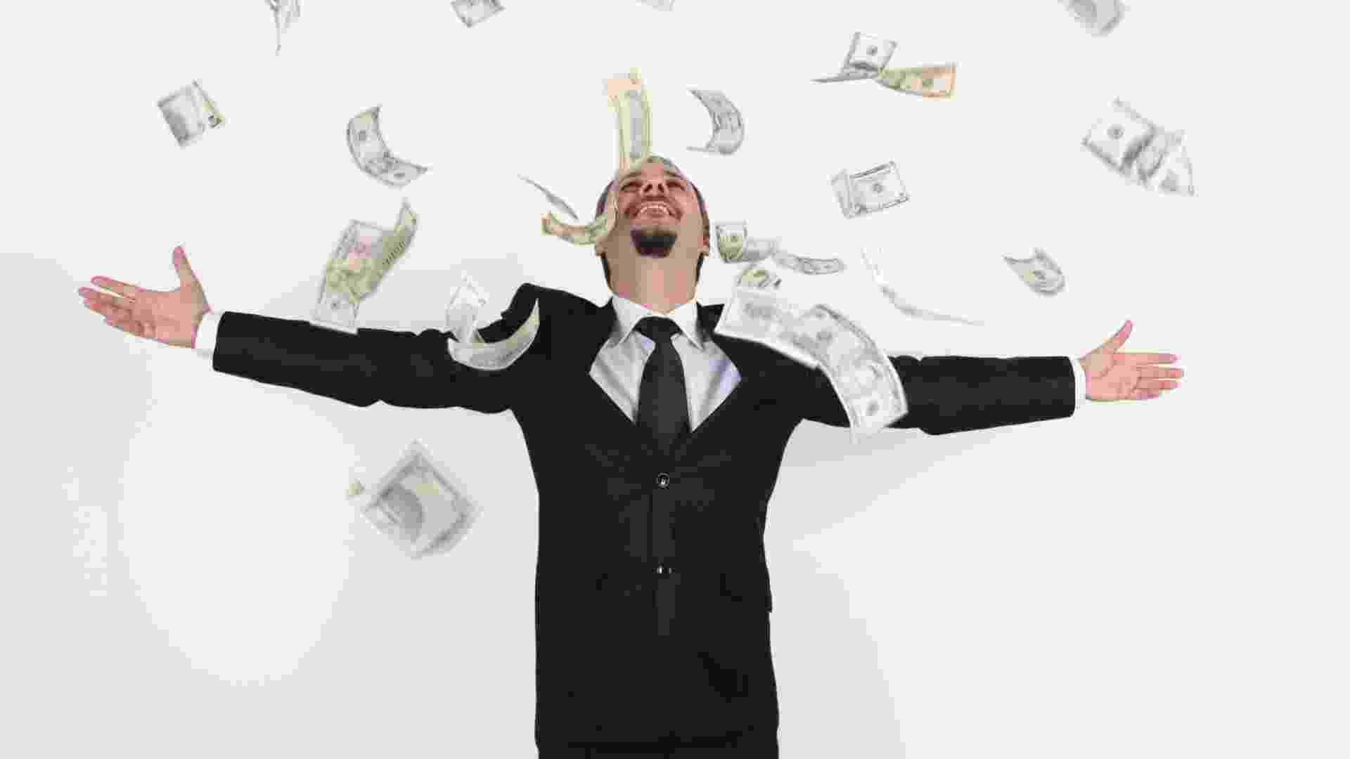 Homem rico faz chuva com dinheiro - Thinkstock