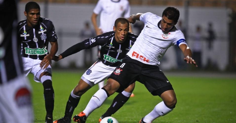 Paulinho tenta o domínio da bola marcado de perto por jogador do Figueirense, em jogo no Pacaembu