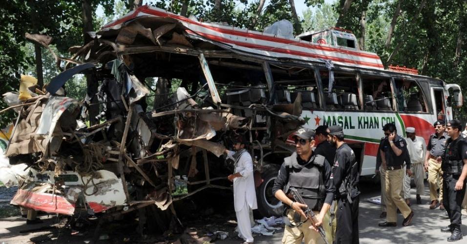 8.jun.2012 - Agentes de segurança examinam destroços de ônibus destruído após explosão de bomba em Peshawar, no Paquistão