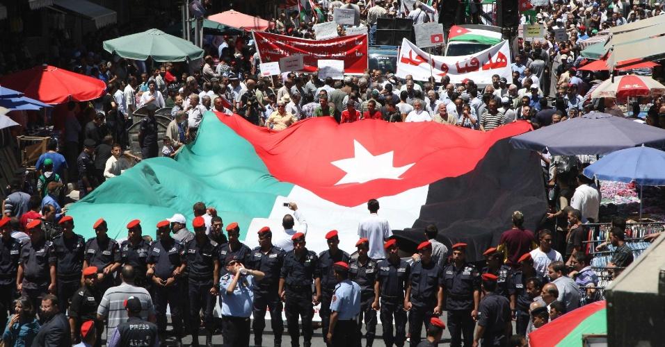 8.jun.2012 - Manifestantes seguram uma imensa bandeira da Jordânia durante protesto para pedir uma reforma política no país