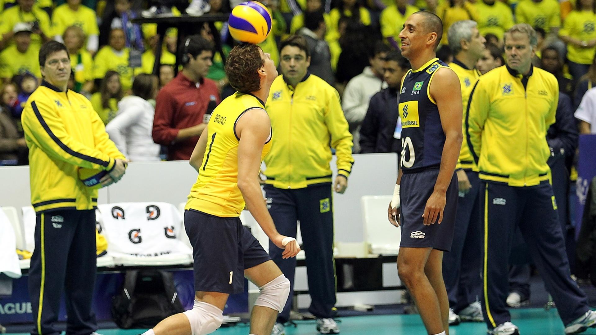 Bruninho, demonstrando equilíbrio com a bola, é observado por Serginho antes do início da partida do Brasil contra o Canadá pela Liga Mundial de Vôlei
