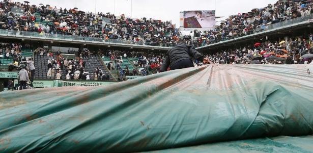 Voluntários cobrem quadra em Roland Garros para proteger o saibro da chuva