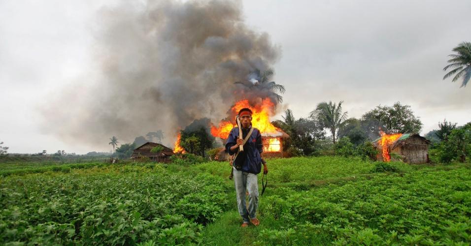 11.jun.2012 - Homem da etnia Rakhine caminha com arma feita manualmente em frente a residências em chamas durante confrontos entre budistas e muçulmanos em Sittwe (Mianmar)
