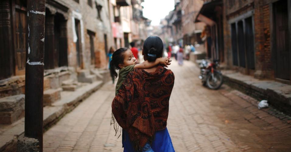 11.jun.2012 - Mulher carrega sua filha no colo pelas ruas de Bhaktapur, no Nepal