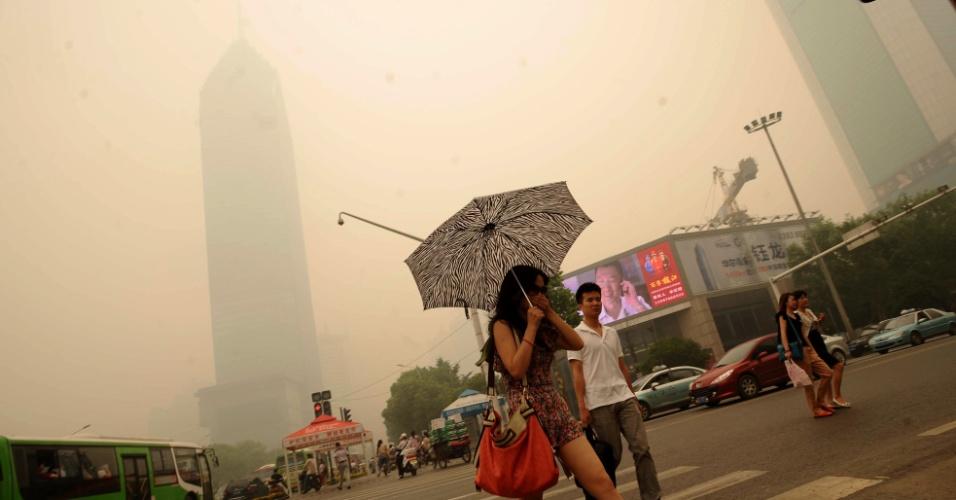 11.jun.2012 - Mulher cobre a boca ao atravessar a rua em Wuhan, cidade chinesa que se viu nesta segunda-feira subitamente envolvida por uma espessa nuvem amarelada, o que provocou inúmeros rumores e preocupações entre os habitantes
