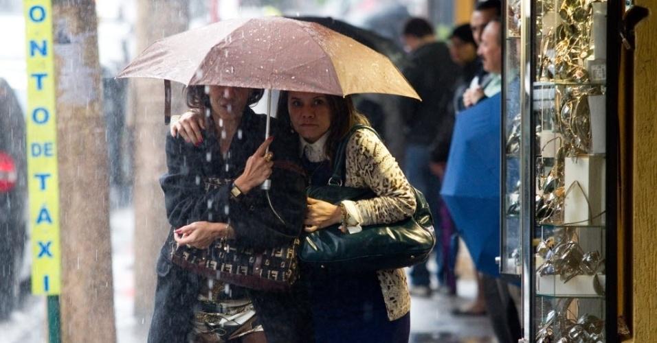11.jun.2012 - Mulheres se protegem sob o mesmo guarda-chuva durante tempestade que atingiu São Paulo nesta segunda-feira (11)