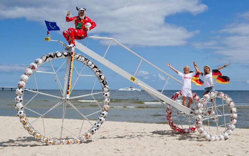 11.jun.2012 - O designer de bicicletas alemão Dieter Senft (à esquerda) fez um triciclo cujas rodas são compostas com cem bolas de futebol e pode entrar para o Livro dos Recordes com sua criação