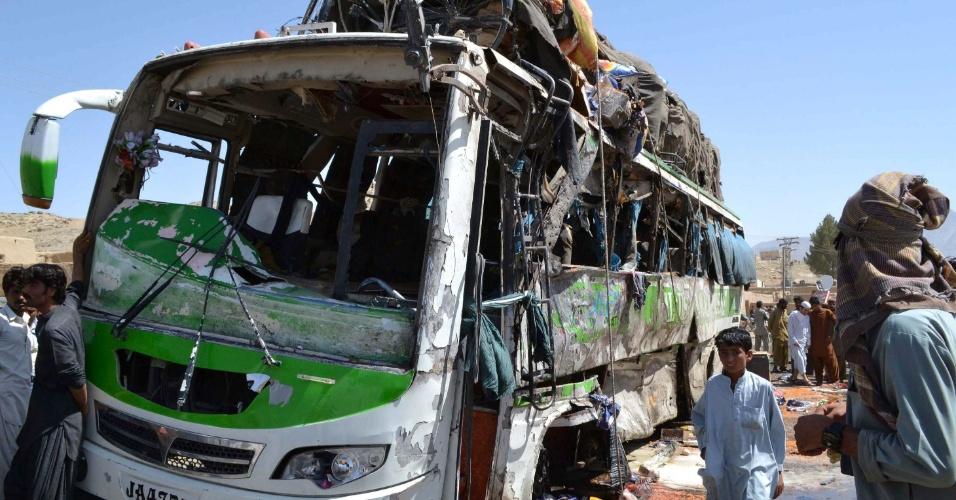 11.jun.2012 - Paquistaneses observam restos de ônibus alto de bomba ativada por controle remoto em Mastung, no Paquistão