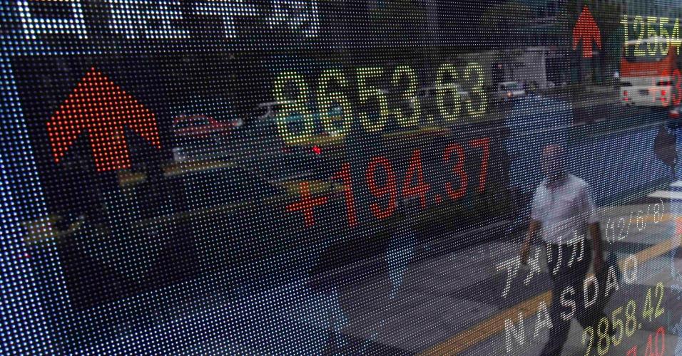 11.jun.2012 - Pedestre passa em frente a placar eletrônico do lado de fora de corretora em Tóquio, no Japão