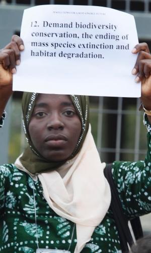 12.jun -Jovem segura cartaz fazendo apelo pela conservação da biodiversidade em manifestação no Riocentro