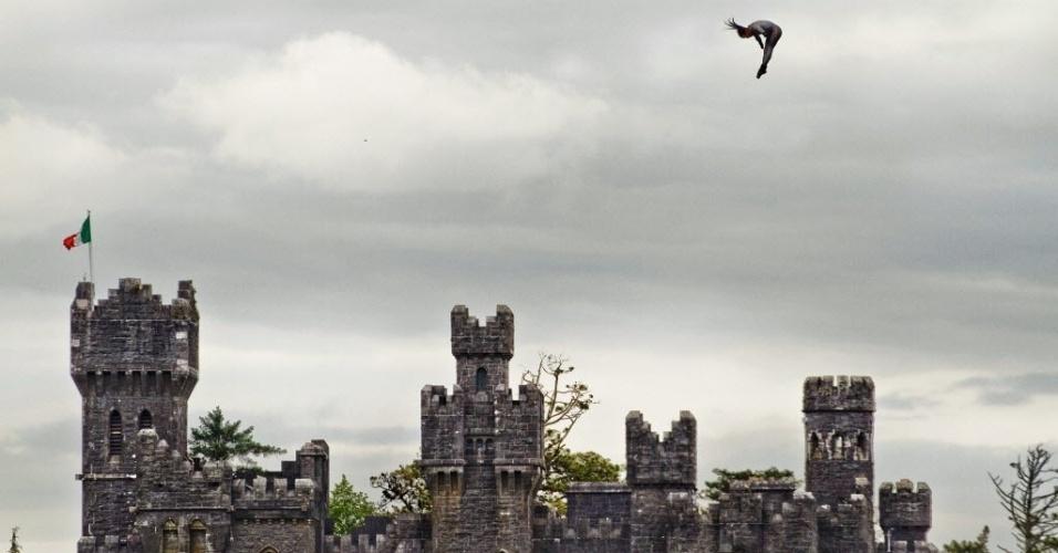 12.jun.2012 - Em foto tirada na segunda-feira (11) e divulgada nesta terça-feira (12), o campeão mundial de saltos ornamentais, o colombiano Orlando Duque, mergulha de um helicóptero a uma altura de 23 metros em frente ao castelo Ashford, na Irlanda, durante treino para evento competitivo de uma marca de bebida energética