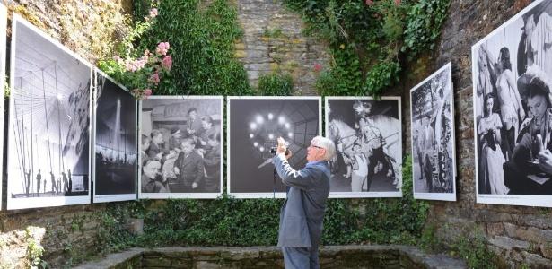 Homem observa imagens do pintor francês Robert Doisneau  - AFP Photo/ Thomas Bregardis