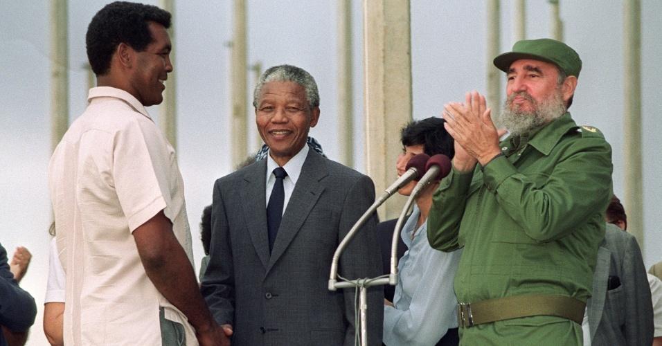 O boxeador Teofilo Stevenson cumprimenta Nelson Mandela, observado pelo ex-presidente de Cuba Fidel Castro, em uma visita do ex-presidente sul-africano à ilha em 1991