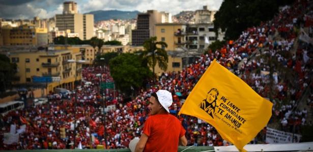 11.jun.2012 - Eleitor segura bandeira em apoio a Hugo Chávez e observa multidão em comício em Caracas, Venezuela