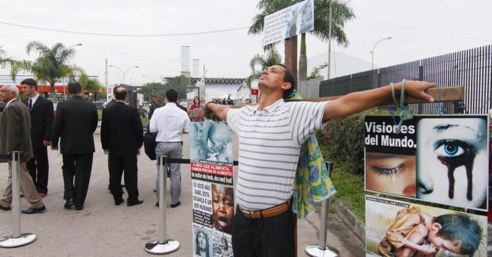"""13.jun.2012 - """"Crucificado"""", o mineiro André Luiz faz protesto na entrada do Riocentro. Ele diz que vai permanecer de pé no local até o dia 18"""