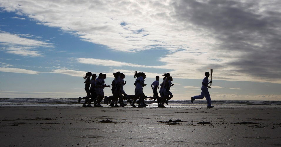 Tocha olímpica passa pela praia de West Sands, na Escócia, recriando a clássica cena de abertura do filme