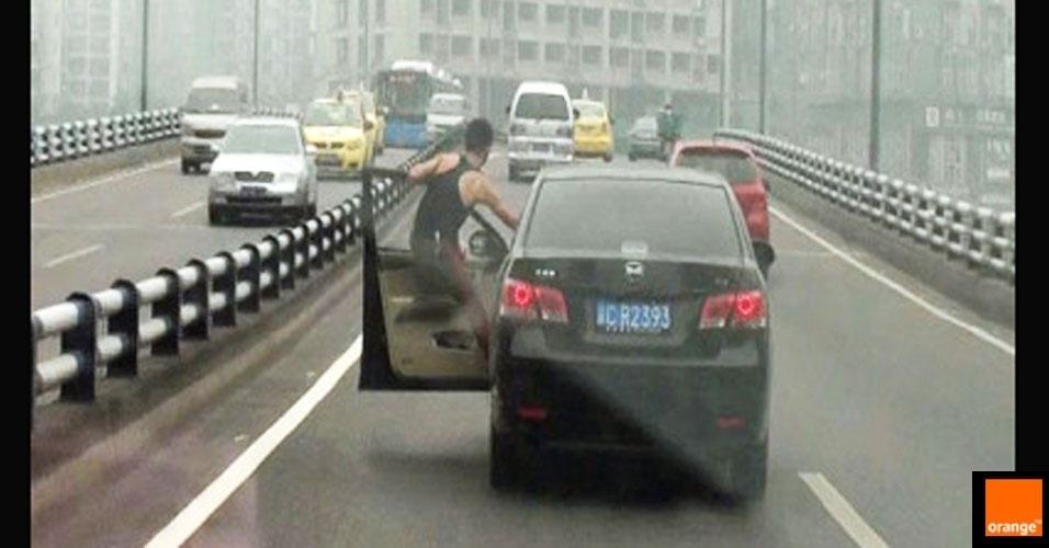 14.jun.2012 - A polícia da China está à procura desse motorista, que foi flagrado dirigindo seu carro com o corpo do lado de fora do veículo. Como ele consegue?
