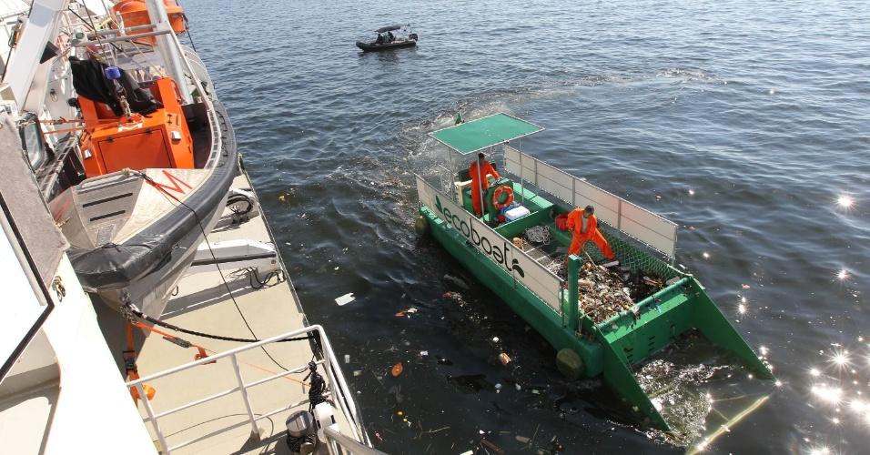 14.jun.2012 - Balsa tenta limpar o lixo da baía junto ao navio do Greenpeace
