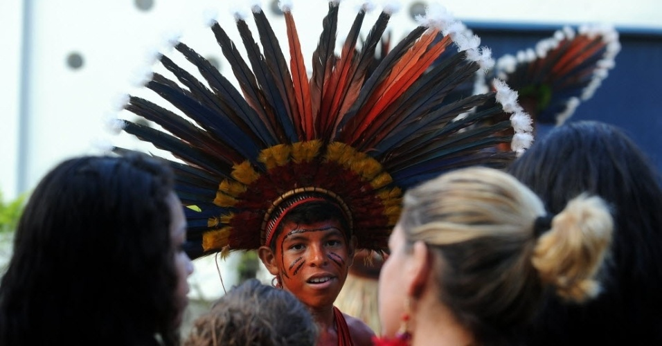 14.jun.2012 - Índio da etnia Bororo é observado por participantes da Rio+20 enquanto se prepara para participar dos jogos verdes nesta quarta-feira