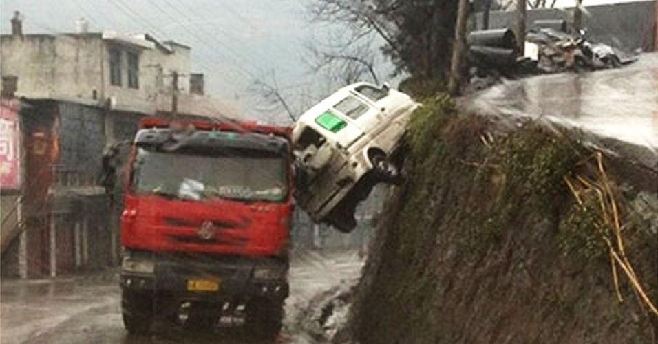 """14.jun.2012 - Numa manobra arriscada, um motorista conseguiu mergulhar sua van para fora da via numa montanha na China, mas teve a sorte de ser """"salvo"""" por um caminhão que passava pela pista de baixo no exato momento da queda"""