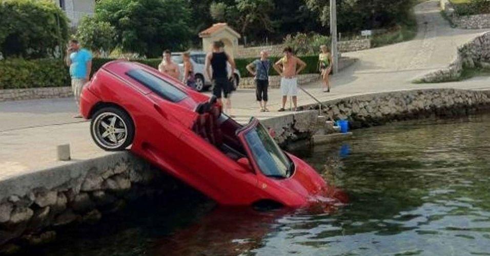 14.jun.2012 - Uma Ferrari estacionada à beira do porto de uma ilha na Croácia foi atingida por uma van e caiu de nariz na água. O carro custa o equivalente a R$ 300 mil
