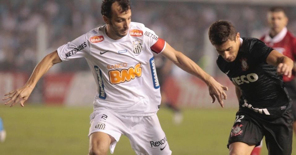 Edu Dracena, zagueiro do Santos, disputa a jogada com o meia Alex, do Corinthians