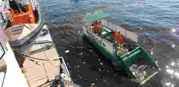Funcionários recolhem lixo despejado em torno do navio do Greenpeace, no Rio de Janeiro - Júlio César Guimarães/UOL