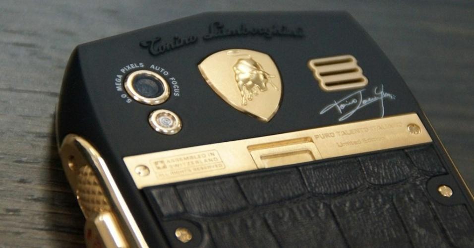 Detalhe da câmera de 5 megapixels do smartphone Lamborghini TL 700.Logotipo da marca tem detalhes em ouro e região da tampa da bateria é confeccionada com pelo de crododilo
