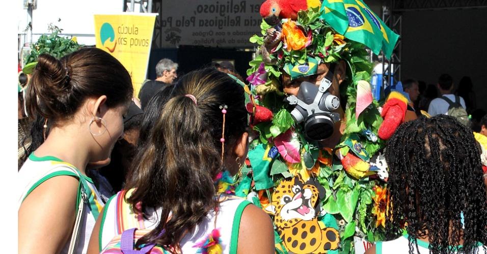 16.jun.2012 - Crianças prestam atenção em manifestante vestido de floresta na Cúpula dos Povos, um dos maiores eventos paralelos da Rio+20, Conferência da ONU sobre Desenvolvimento Sustentável