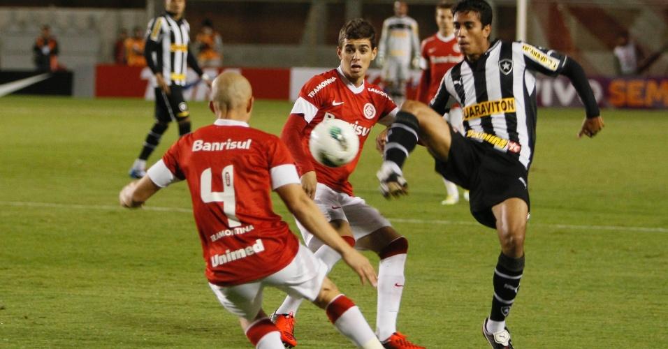 Meia Oscar (centro) observa disputa de bola na partida entre Inter e Botafogo