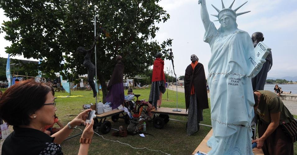 """17.jun.2012 - Mulher fotografa réplica da Estátua da Liberdade segurando um livro com os dizeres """"Liberdade para Poluir"""" na Cúpula dos Povos, um dos maiores eventos paralelos da Rio+20, Conferência da ONU sobre Desenvolvimento Sustentável"""