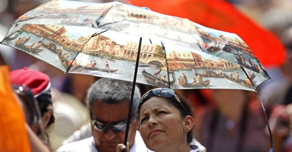 Mulher se protege do sol com uma sombrinha, que mostra uma cena veneziana, enquanto acompanha o discurso do papa Bento 16, no Vaticano