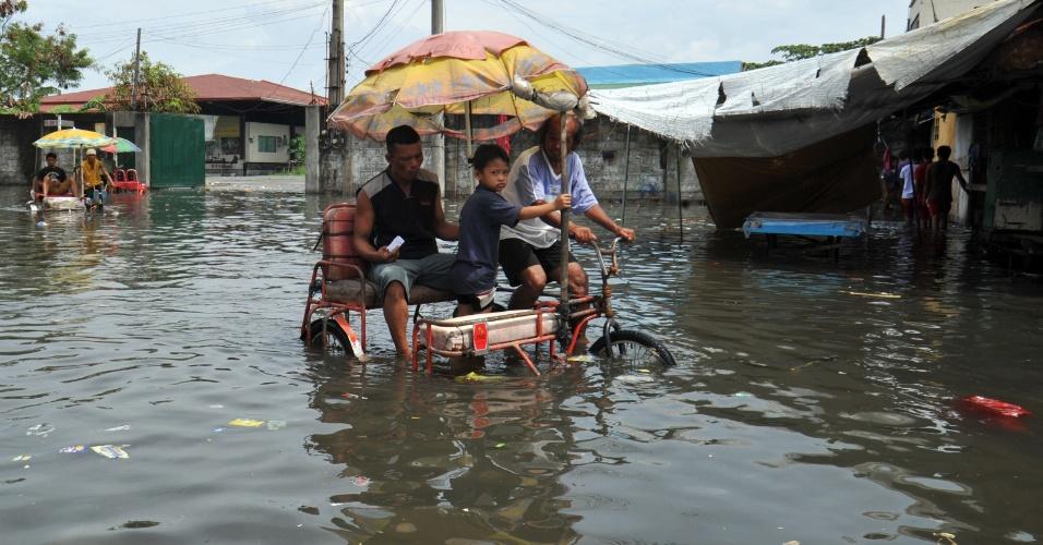 18.jun.2012 - Filipinos andam de triciclo em rua alagada em Manila, capital das Filipinas