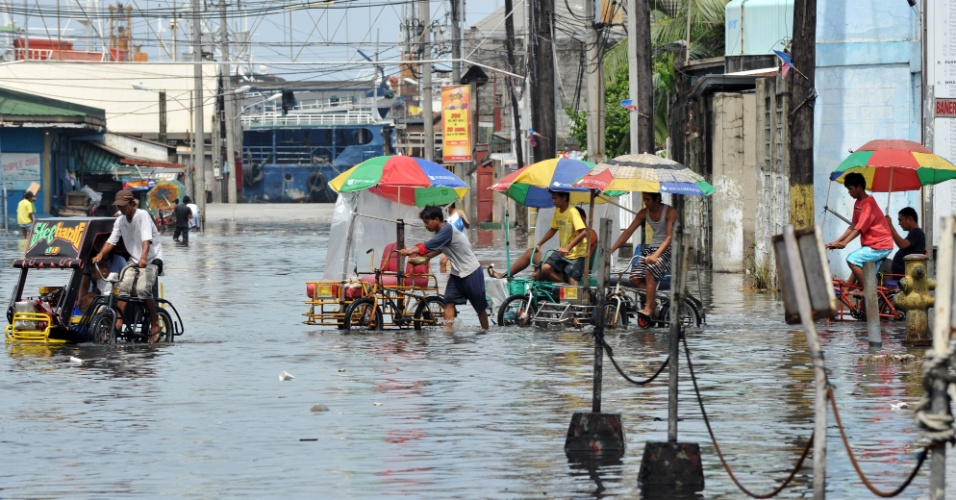 18.jun.2012 - Filipinos levam seus triciclos por rua alagada em Manila, capital das Filipinas