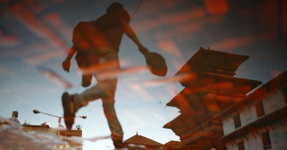 18.jun.2012 - Silhueta de homem é refletida em poça de água em Katmandu, capital do Nepal