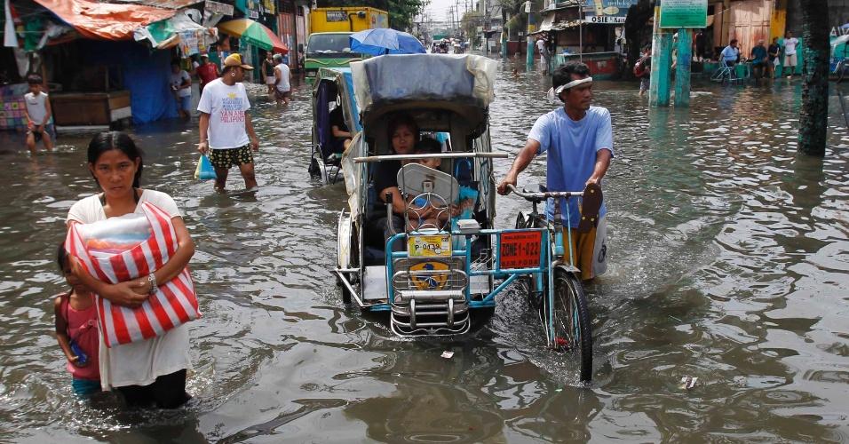 18.jun.2012 - Filipinos caminham em rua alagada no subúrbio de Malabon, ao norte de Manila, capital das Filipinas