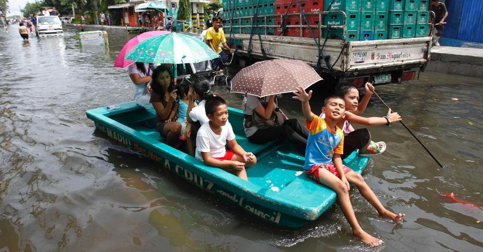 18.jun.2012 - Filipinos usam pequeno barco para se locomover em rua alagada no subúrbio de Malabon, ao norte de Manila, capital das Filipina
