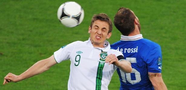Kevin Doyle disputa bola no ar com Daniele De Rossi em jogo da seleção