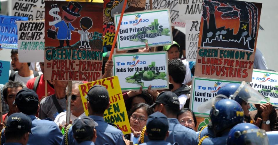 """20.jun.2012 - Ativistas filipinos seguram cartazes em protesto contra a """"economia verde"""". A ação foi realizada para coincidir com a abertura oficial da Rio+20, Conferência da ONU sobre Desenvolvimento Sustentável"""