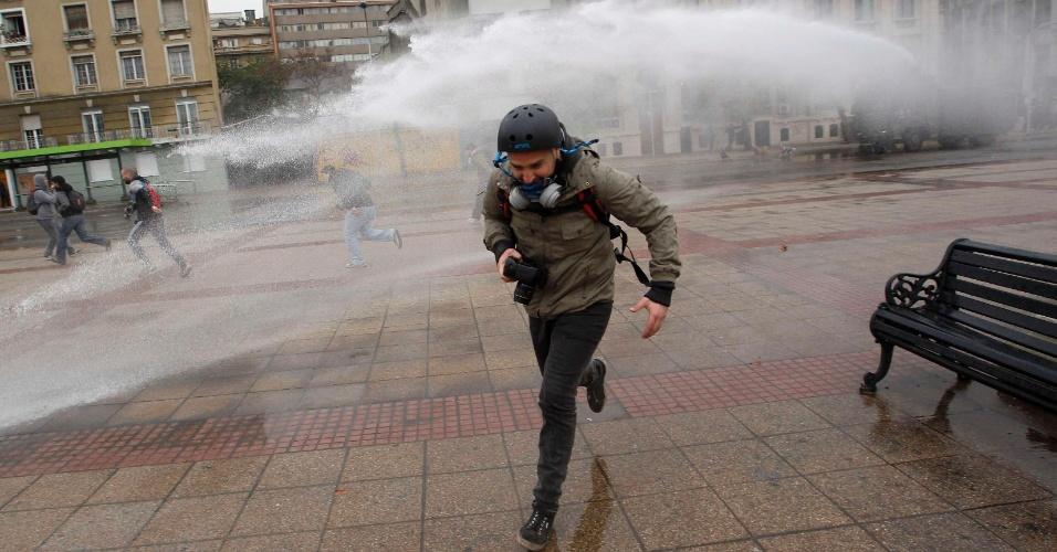 Estudantes secundários marcharam nesta quarta-feira (20) pelo centro de Santiago, no Chile, para pedir melhorias no sistema público de ensino. O protesto terminou em confronto com a polícia. Na foto, fotógrafo tenta fugir de jato de água