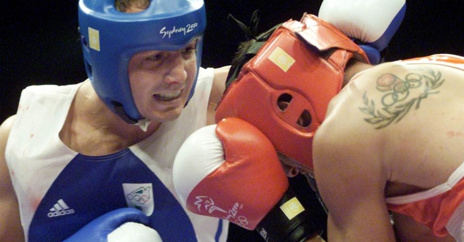 Sven Paris, na foto de vermelho, exibe seu símbolo olímpico estilizado com uma luva de boxe durante os Jogos Olímpicos de 2000, em Sydney