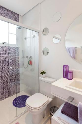 O banheiro da suíte da menina mantém tons lilás do quarto, com mescla de pastilhas lilás e roxas, assentadas na largura da janela. A casa em São Caetano do Sul (SP) tem reforma assinada pela arquiteta Mayra Lopes