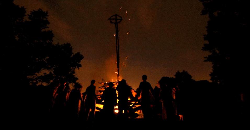 23.jun.2012 - Bielorrussos dançam em volta de fogueira em região rural de Gomel, a 350 km de Minsk, capital de Belarus. A dança marca a noite Ivana Kupala, um antigo ritual pagão, no qual as pessoas se envolvem em mantas, pulam fogueira e se banham em rios e lagos