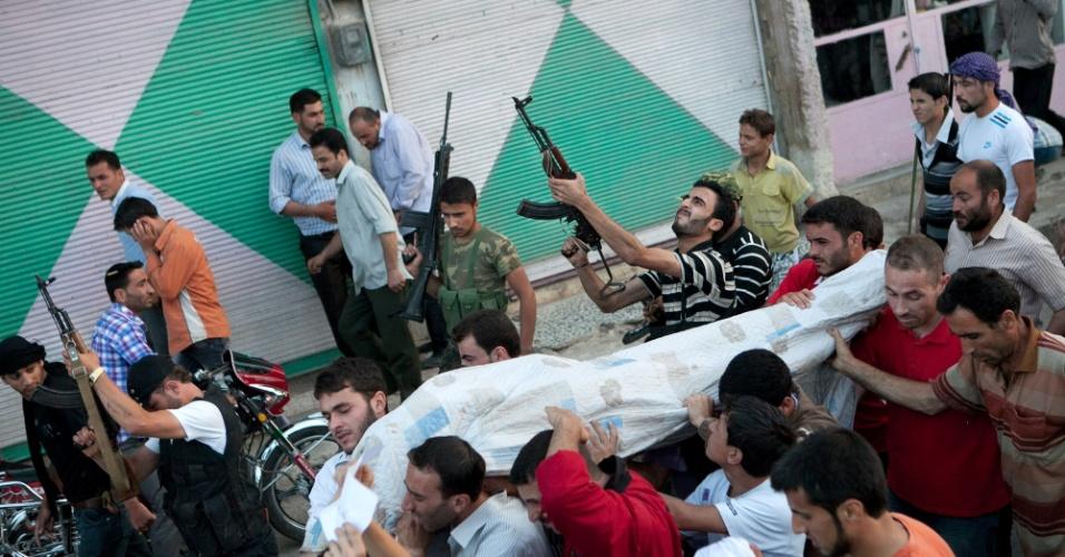 23.jun.2012 - Combatentes sírios atiram para cima durante funeral de um funcionário supostamente baleado na cabeça por um atirador do exército sírio, durante uma manifestação anti-governo no norte da Síria