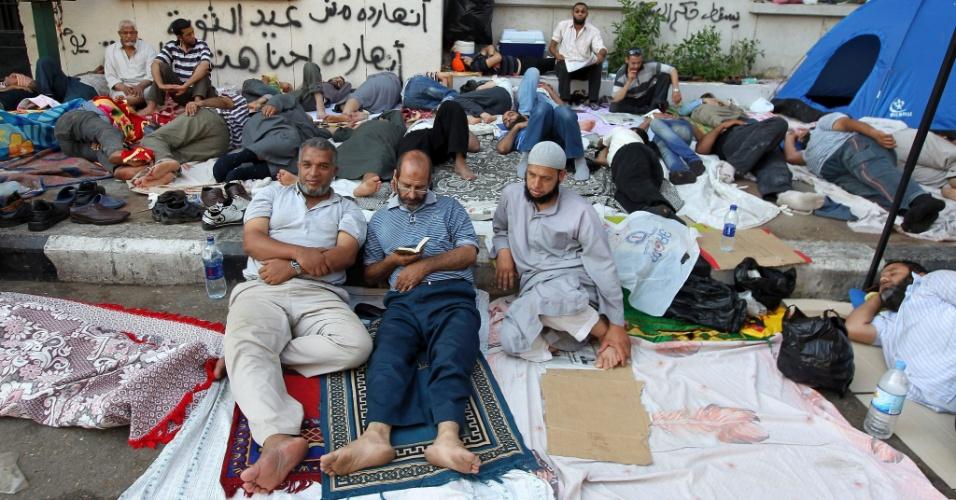 23.jun.2012 - Egípcios leem o Corão enquanto outros dormem neste sábado (23), na Praça Tahrir, em Cairo